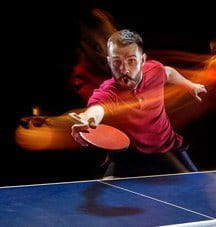 A table tennis player hitting the ball