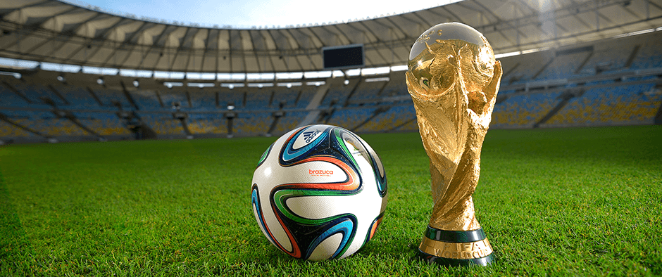 A ball and the World Cup trophy on a football pitch.