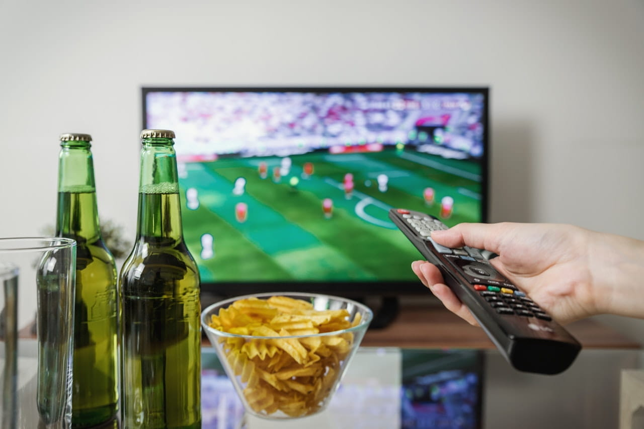 A football match on tv with alcohol in the foreground