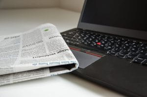 A laptop and newspaper