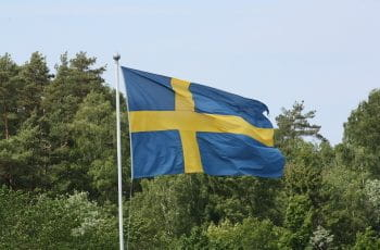 Swedish flag with trees in the background.
