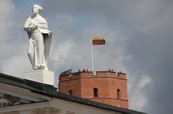 Lithuanian flag on a building with a statue