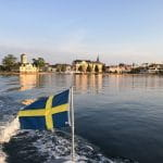 Swedish flag on a boat with buildings in the backgroun